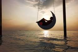 Houpačka v moři při západu slunce na Maledivách