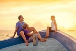 rodina na lodi při západu