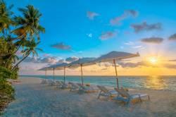 lehátka na pláži západ slunce Maledivy