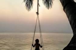 dítě na houpačce na pláži