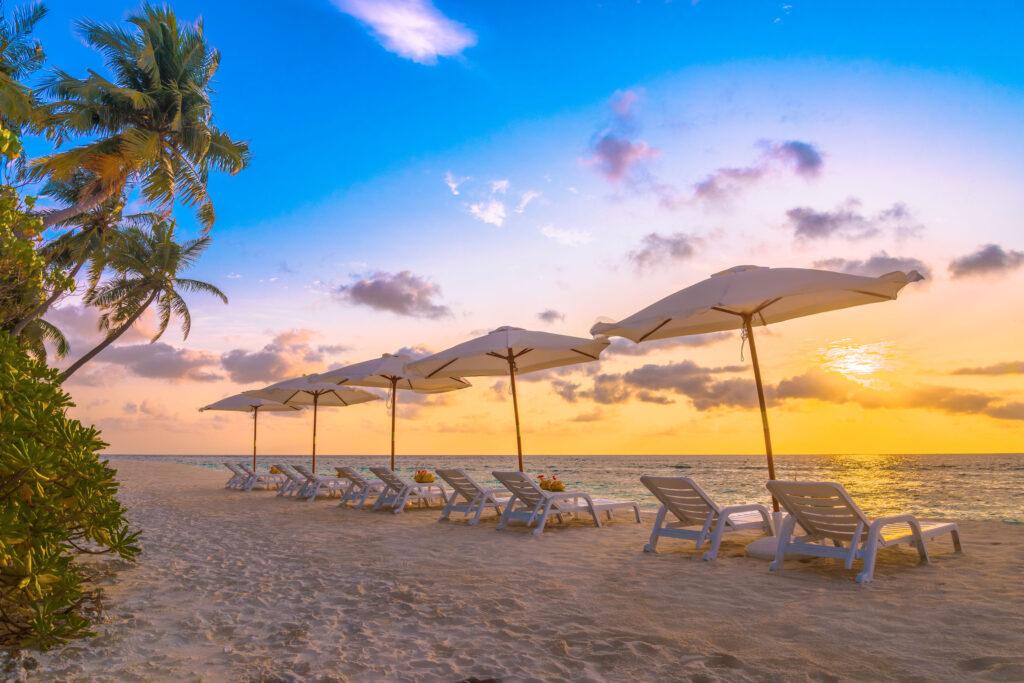 lehátka na pláži Malediv při západu slunce